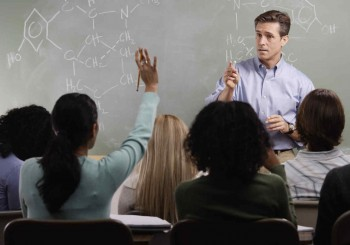 Chemistry Teacher with Students in Class --- Image by © Royalty-Free/Corbis